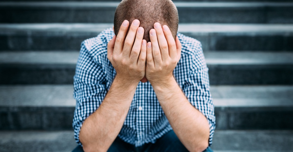 40346537 - outdoor portrait of sad young man covering his face with hands sitting on stairs. selective focus on hands. sadness, despair, tragedy concept