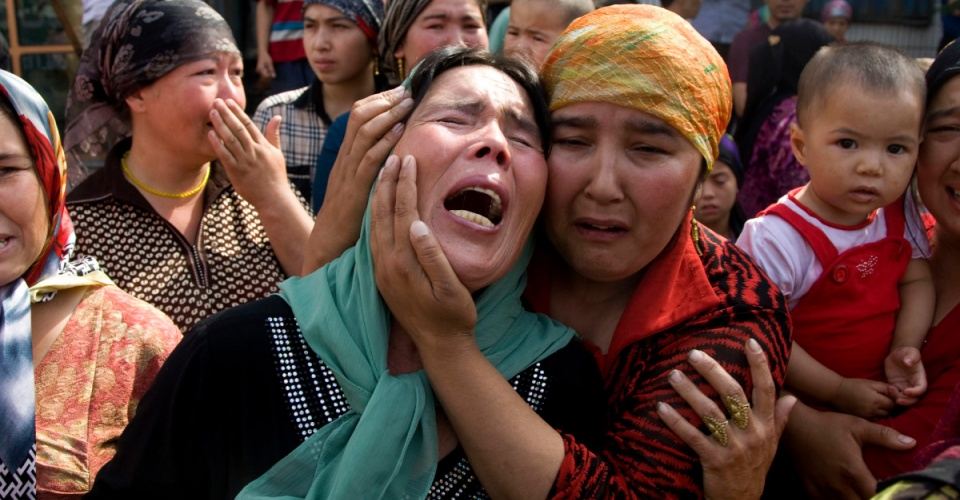 Uigher  women grieving for their men who they claim were taken away by the Chinese authorities after Sunday's protest in Urumqi, China, Tuesday, July 7 , 2009. (AP Photo/Ng Han Guan)