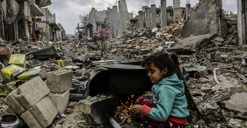 TOPSHOTS Kurdish Syrian girls are pictured among destroyed buildings in the Syrian Kurdish town of Kobane, also known as Ain al-Arab, on March 22, 2015. AFP PHOTO/YASIN AKGULYASIN AKGUL/AFP/Getty Images