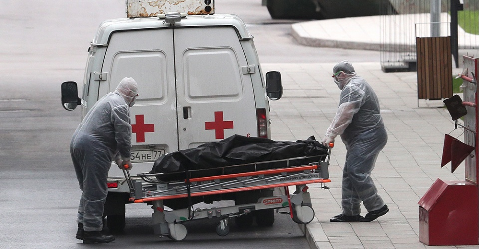 """MOSCOW, RUSSIA – APRIL 25, 2020: Medical staff worker in protective gear roll a stretcher with the body of a deceased patient at the Novomoskovsky multipurpose medical centre for patients with suspected COVID-19 coronavirus infection, in Kommunarka, Novomoskovsky Administrative District of Moscow. As of 25 April 2020, Russia has reported more than 68,700 confirmed cases of the novel coronavirus, with more than 36,800 confirmed cases in Moscow. Gavriil Grigorov/TASS  Россия. Москва. Медицинский персонал в защитных костюмах везет тело умершего пациента в патологоанатомический корпус многопрофильного медицинского центра """"Новомосковский"""". Гавриил Григоров/ТАСС"""