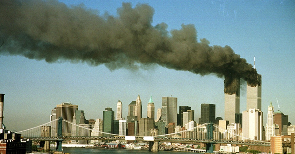 The towers of the World Trade Center billow smoke shortly after being struck by hijacked commercial airplanes in New York in this file photo taken on September 11, 2001. The East River and Manhattan Bridge are in the foreground. This year's anniversary of the September 11 attacks in New York and Washington will echo the first one, with silence for the moments the planes struck and when the buildings fell, and the reading of 2,792 victims' names. REUTERS/Brad Rickerby-Files  HB/ - RTR2G09